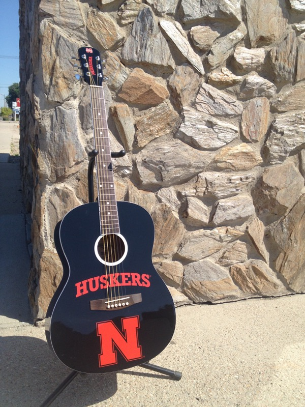 Now ain't that a purty gee-tar? If you play (or even if you don't), how can you call yourself a true Husker fan if you don't have a Husker guitar? The guitar that will be auctioned is #22 on the limited production run of 100 guitars. They aren't too common!